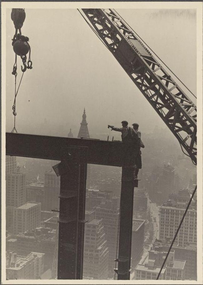 Two Construction Workers At The Corner Of Two Steel Beams Pointing To The Left